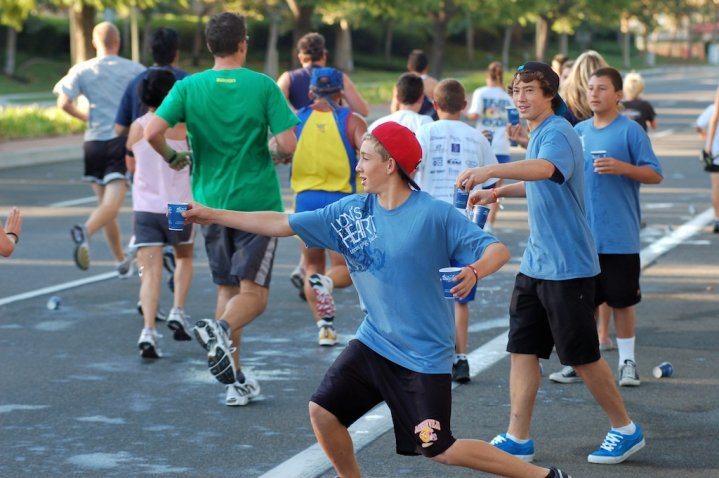 Orange County teen volunteers provide water to marathon runners from the sidelines